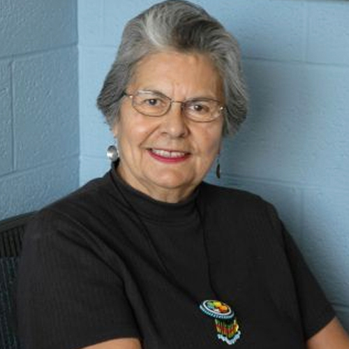 Ada Deer, 2007. A middle aged woman looking confidently at the camera while smiling. Her shirt is black and she wears beaded necklace pendant.
