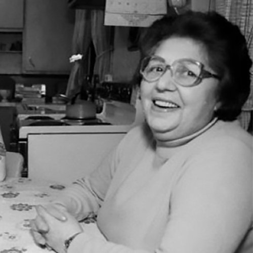 Holocaust survivor Rosa Goldberg Katz in her residence looking quite happy as she sits at her table.