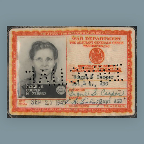 The identification card of Signe S. (Skott) Cooper, 1st Lt., ANC. (First Lieutenan, Army Nurse Corps.) The card was issued SEP 25 1945. Her photograph is on the left, name and signatures on the right. When the card is reversed, the punched holes across the ID spell 'INACTIVE.'