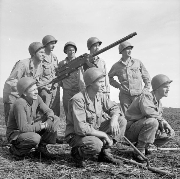 A group of soldiers kneeling around a large gun