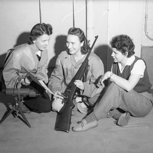 Three white women receiving weapons training during World War II. Women are receiving training on the handling of a rifle.