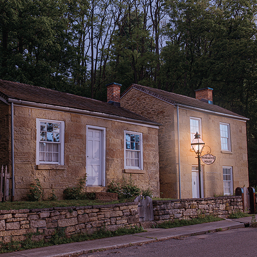 Pendarvis house at dusk,  orange colored brick and white trim windows and doors. A stone wall lines the house next to the road. The lamp is lit.