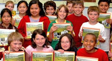 Group of students and teachers holding the 4th-grade history textbook.