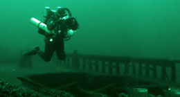 Underwater archeaologist diving underwater to examine a historic shipwreck.