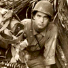 Robert Doyle emerges from a captured Japanese pillbox at Buna, Papua New Guinea. WHI 100824.