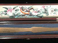 Interior of fan box. Lid is painted with bird and flower details. Cardboard insert in lower portion holds the fan in place while stored.