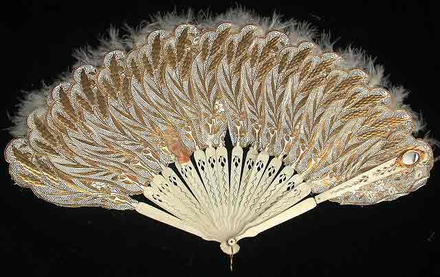 Off white fan with guilded wheat, feathers at the tips, and a small oval mirror embedded on the right.