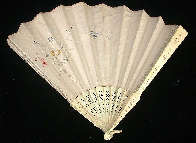 White fan with carved sticks and painted with an assymetrical pattern of pink, yellow and blue delicate long-stemmed wild flowers.