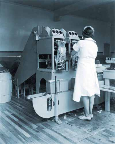 Woman in white dress and hat using a machine to bag Red Dot potato chips.